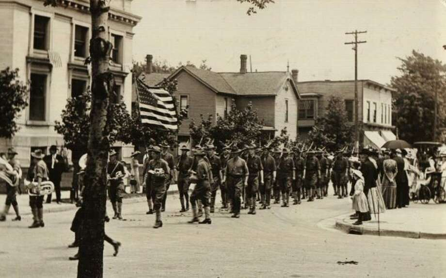 This picture shows an early 1900 Fourth of July Parade that was moving down First Street.