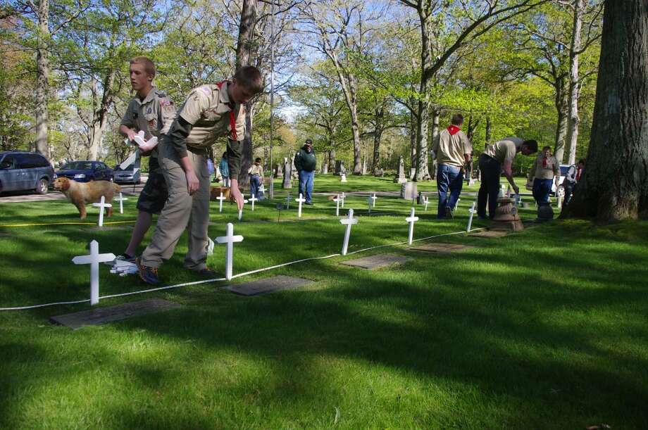 Manistee Boy Scouts repainted the white crosses then placed them on veterans' graves at Oak Grove Cemetery on Thursday. (Dave Yarnell/News Advocate)