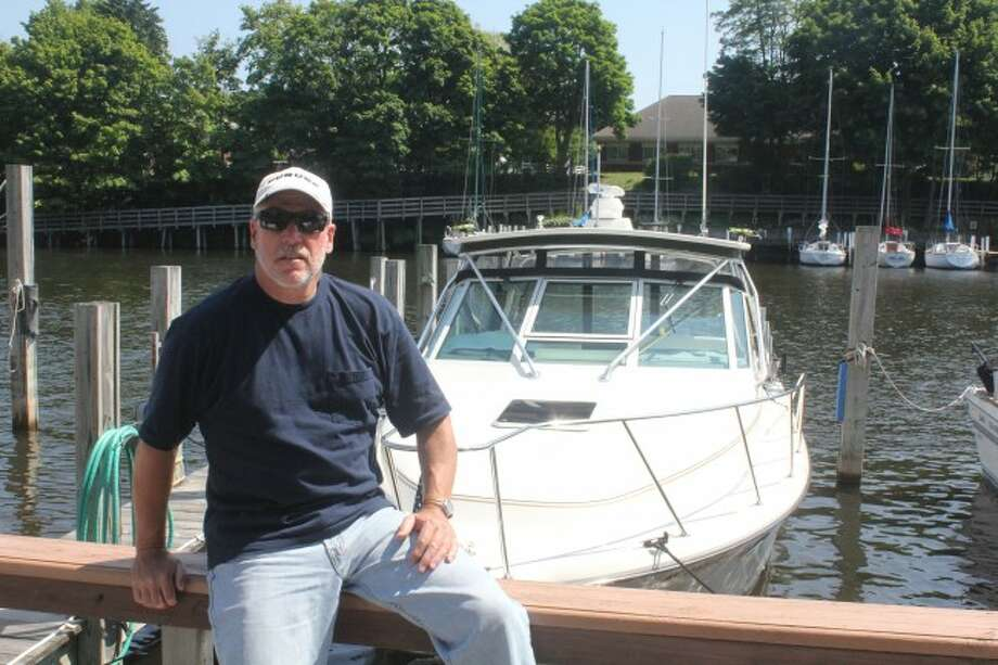 Denny Kuenzer with his boat at Ship Watch Marina in Manistee.