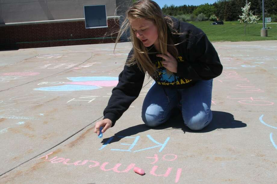 Freshman Allie Zimmerman shows her support during the Mini Relay for Life event held at Manistee High School Friday. The sidewalk in front of the school was covered with names of friends and loved ones written in chalk. (Abigale Racine/Manistee News Advocate)