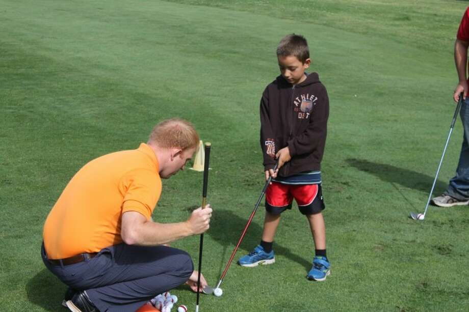 The First Tee Program of Northern Michigan's Seth Jones shows young student Derric on where he should position his club to hit the ball best. The popular program teaches children character and life skills besides how to play golf.