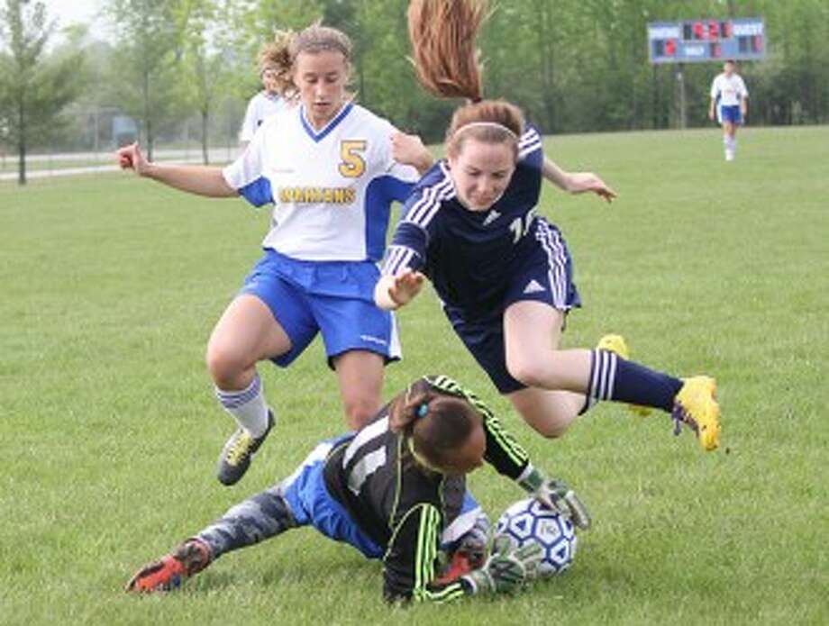 Manistee's Mallory Stefanski (right) collides with Mason County Central goalie Makila Hodges (11) while MCC's Ariel White looks on during Tuesday's Division 3 district quarterfinal. (Dylan Savela/News Advocate)