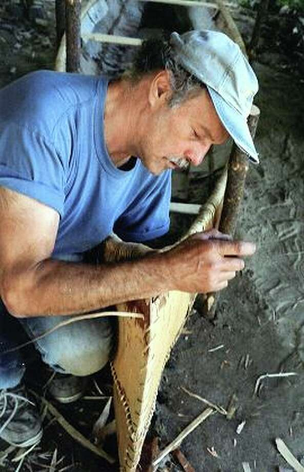 Tom Byers uses spruce roots to lash together two sides of a birch bark canoe.