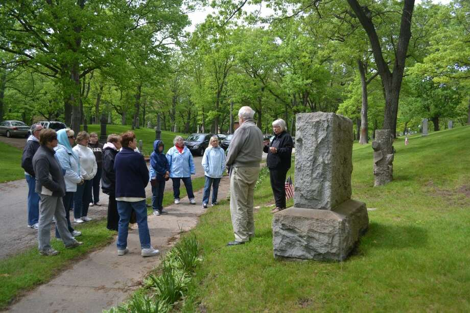 Susan Lund-Coyle and her husband Duane Coyle lead a tour group on Sunday afternoon in Oak Grove Cemetery. The couple has been giving historical tours of the cemetery for the past seven years. (Meg LeDuc/News Advocate)