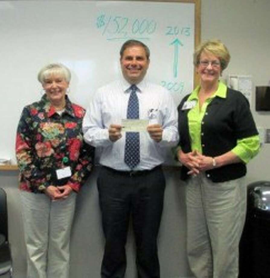 West Shore Medical Center Auxiliary President Elizabeth Tyson (right) and President-Elect Kathleen Jeffreys (left) present West Shore Medical Center President James Barker with a $10,000 check. The check completed the auxiliary's $152,000 pledge to purchase an ambulance. (Courtesy Photo)