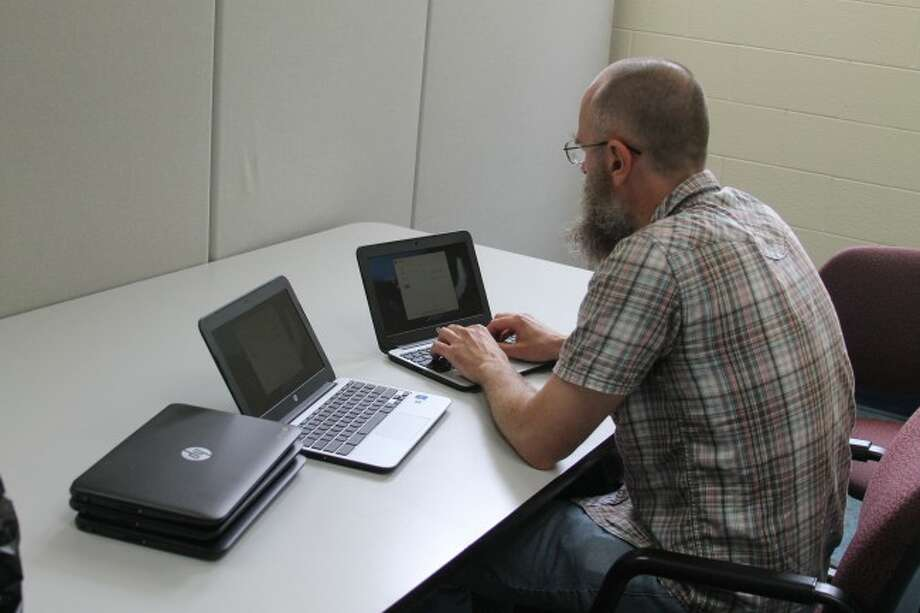 Manistee Intermediate School District Technology Department's Chad VandeHenst makes adjustments to the HP Chromebooks that the Kaleva Norman Dickson and Bear Lake school districts will be using this year in their one-to-one computer programs.