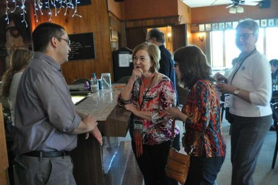 Travis Alden, DDA director, talks with volunteers Jennie Naffie, Anne Mirretti and Meg Voelker at the annual DDA volunteer appreciation dinner Wednesday night.