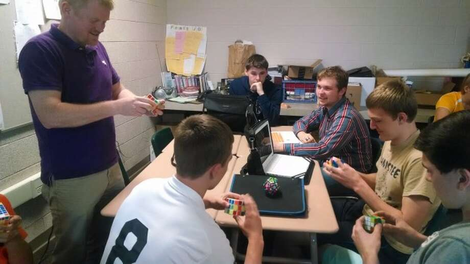Manistee High School teacher Eric Thuemmel watches as some of his students work with Rubik's Cubes. The 1980s craze has caught on at Manistee High School.