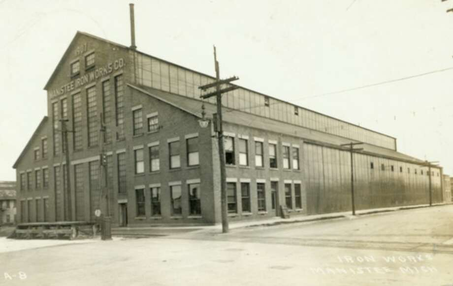The Manistee Iron Works building is shown in this 1920 picture. The Iron Works was a strong industry in this area until its closing. The building still sits empty on the east end of River Street.