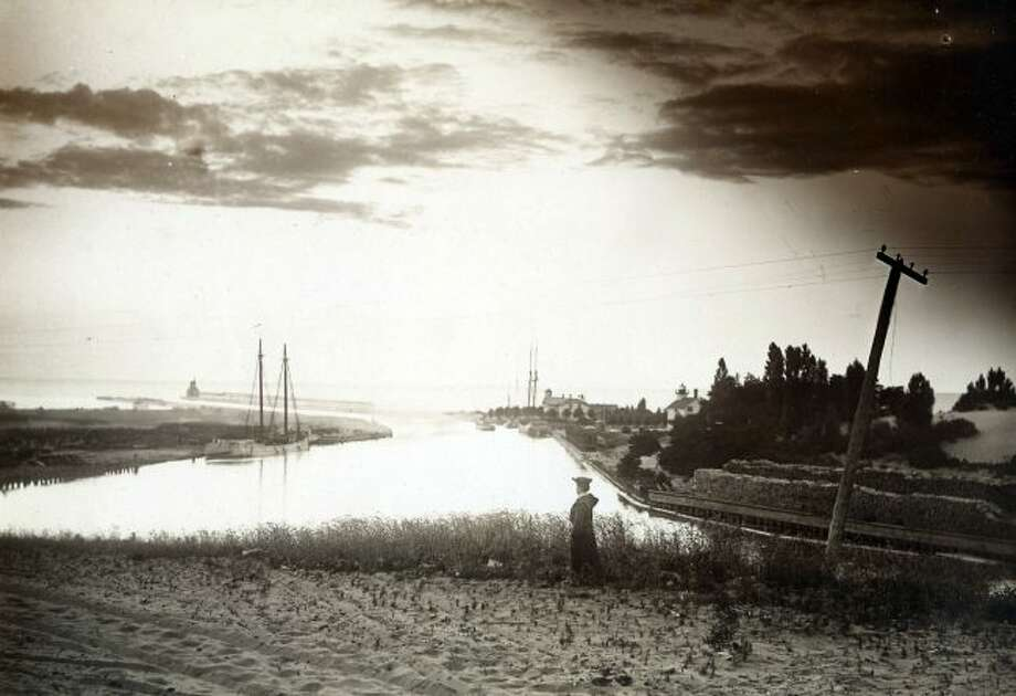 A lone woman stands atop the bluff by First Street Beach in this early 1900 picture overlooking the Manistee Harbor entrance.