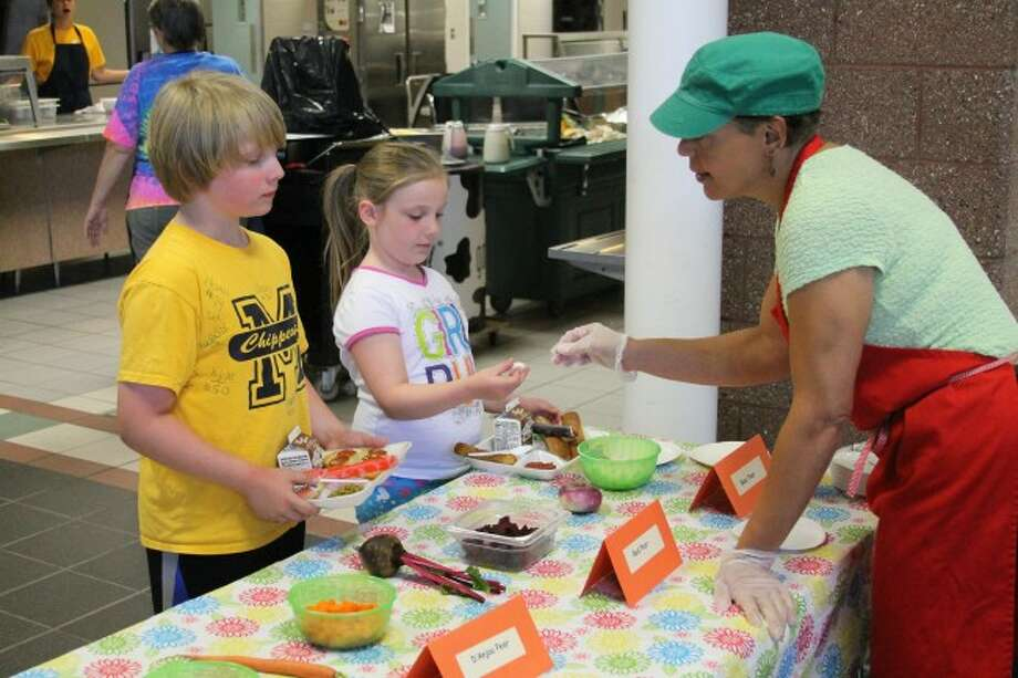 Luke and Gabby Senters try some of the vegetables that District No. 10 Health Department's Holly Joseph has out for the Cooking With Kids program at the Manistee Area Public Schools summer food program.