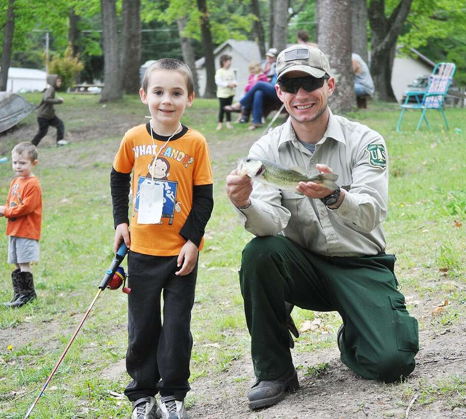 Sammy Strange, 5, of Wellston, caught this 13-inch bass held by Manistee ranger Chris Warnock at the eighth annual Bobbie Brown Memorial Fishing Tournament in Wellston.