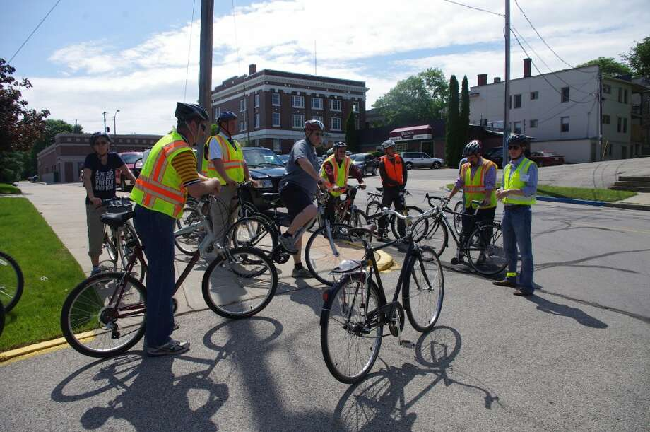 The participants in Training Wheels 2013: Bicycle Facility Design Training assemble outside of Manistee City Hall, ready for a six-mile ride around Manistee to look at various bicycle facilities. (Dave Yarnell/News Advocate)