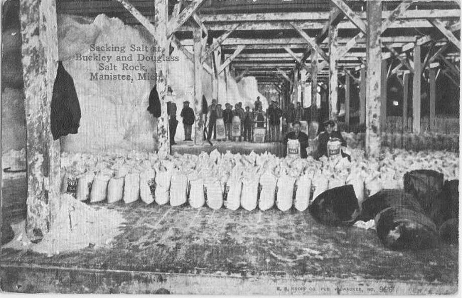 Shown is salt sacking taking place at the Buckley and Douglas Salt Sacking Rock in the late 1890s.