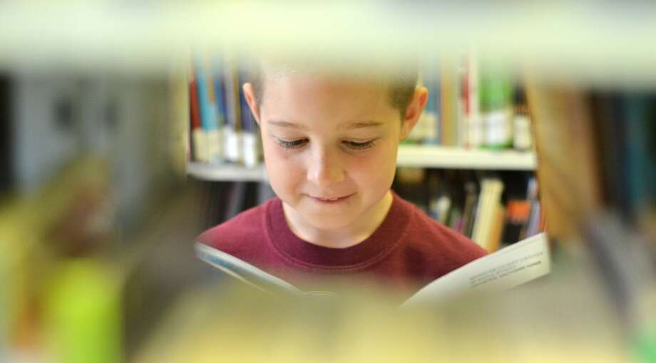 Cole Mortensen, 10, peeks through the bookshelves at the Manistee County Library. (Courtesy photos/David Navadeh)
