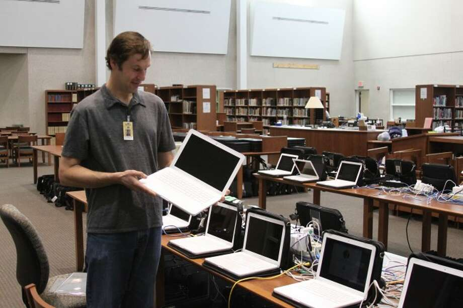 Manistee Area Public Schools Technology Director Ken Blakey-Shell looks over some of the computers that will be sold off to the public on Monday.