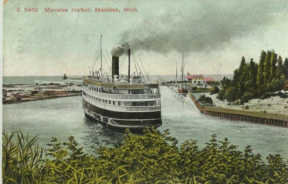 A steamer churns its way out out the Manistee harbor in this 1890s depiction. Located on the north side of the channel is railroad cars filled with lumber ready to be shipped to cities across Lake Michigan.