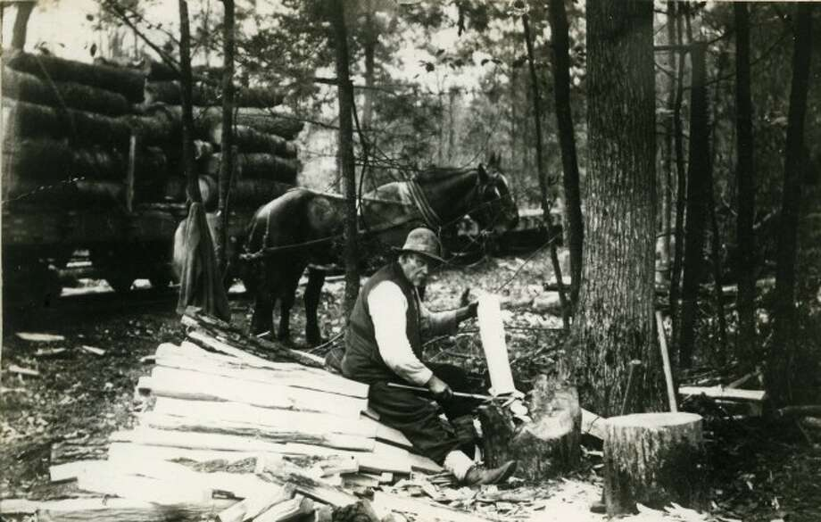 A lone lumberjack splits firewood in front of a load of logs that await shipping to the mill aboard a narrow gauge railroad in Manistee County. The lumbering era in Manistee County helped develop the area.