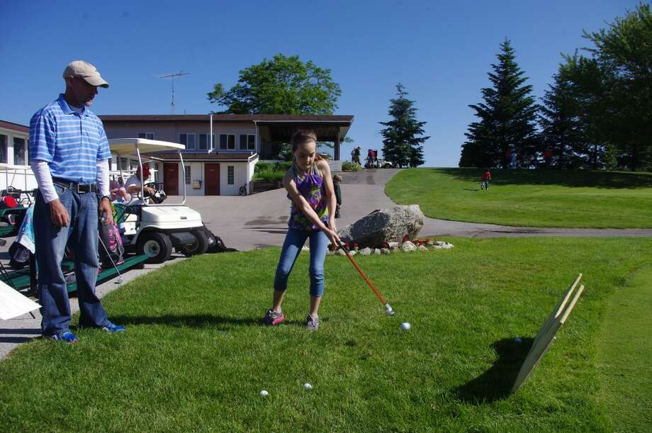 Brynn O'Donnell chips the golf ball toward the cup under the watchful eye of Eric Ross, golf professional at the Heathlands Golf Course. The week-long youth golf clinic, held at Bear Lake Highlands Golf Course, ended on Friday. (Dave Yarnell/News Advocate)