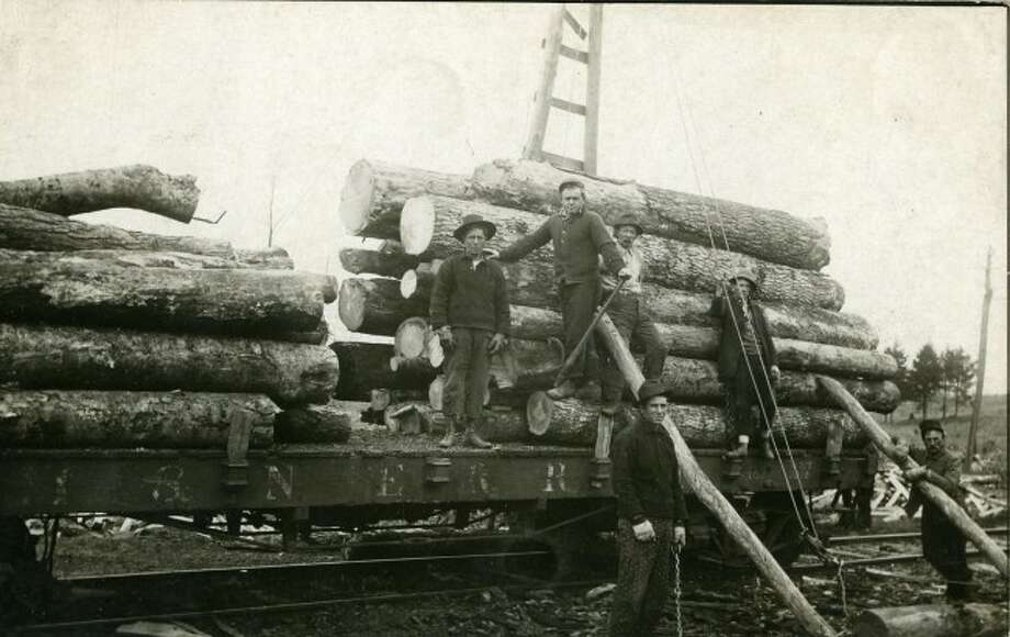 This group of lumberjacks proudly pose with another stack of logs that are being shipped off to the sawmill.