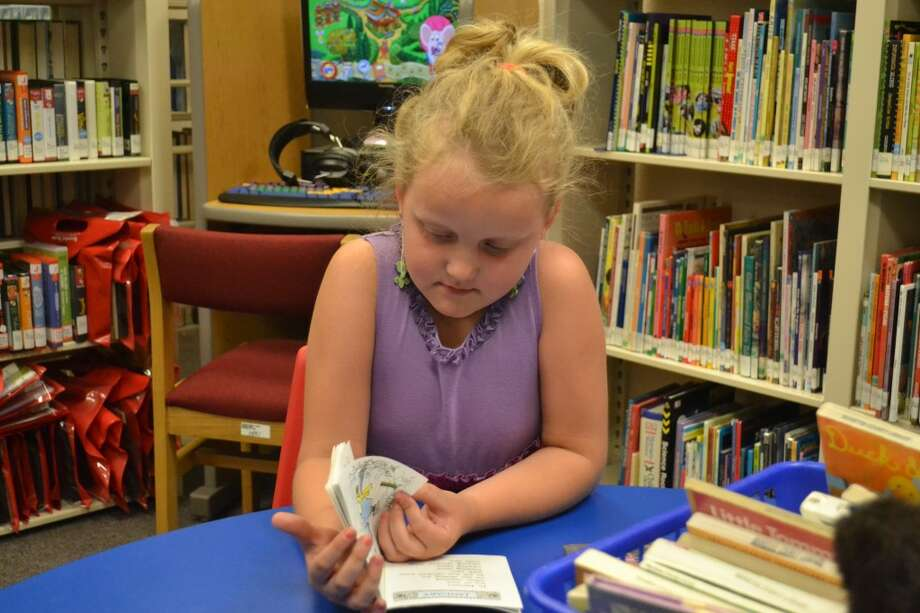 A child reads on Thursday at the Wellston Branch Library, part of the Norman Township Community Center. (Meg LeDuc/News Advocate)