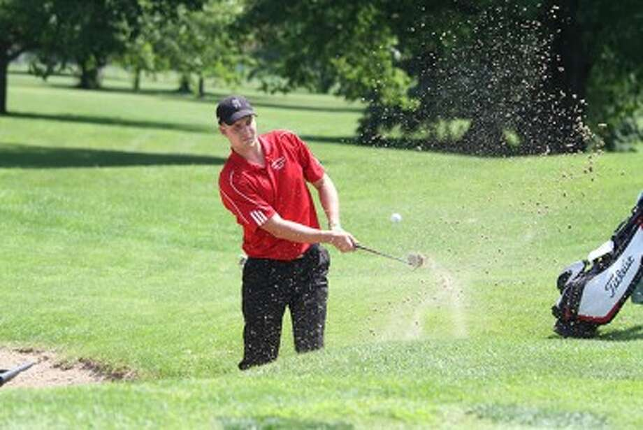 Manistee Catholic Central senior Zack Bialik blasts out of the bunker on No. 16 at Michigan State's Forest Akers East during Friday's opening round of the Division 4 state finals. (Matt Wenzel/News Advocate)