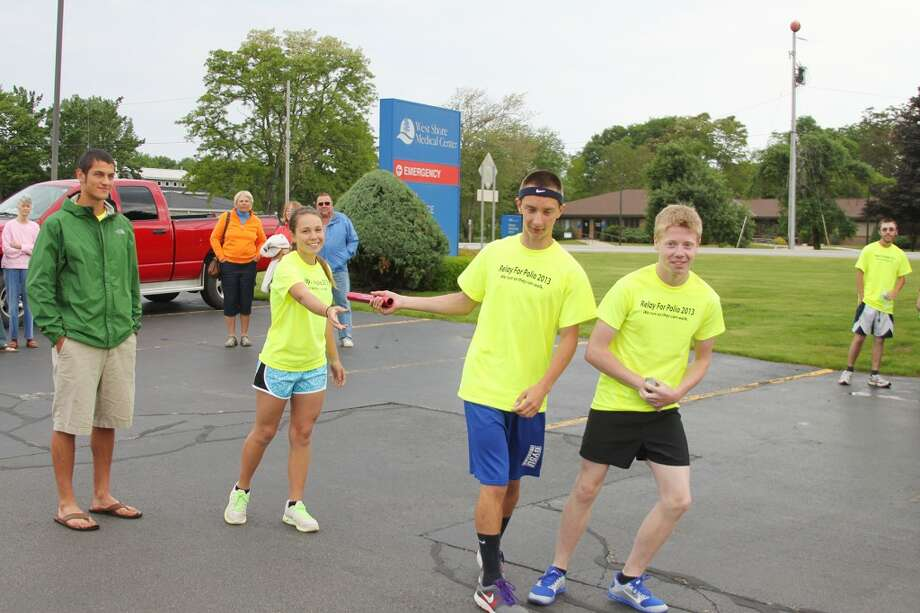 Relay Run for Polio organizers Ismael Halaweh and Makayla Huddleston who are members of the Benzie Central Track team and the Rotary Interact Club hand off the baton to Colin Bachinski and Bryce Cameron for the start of the 72 mile run.