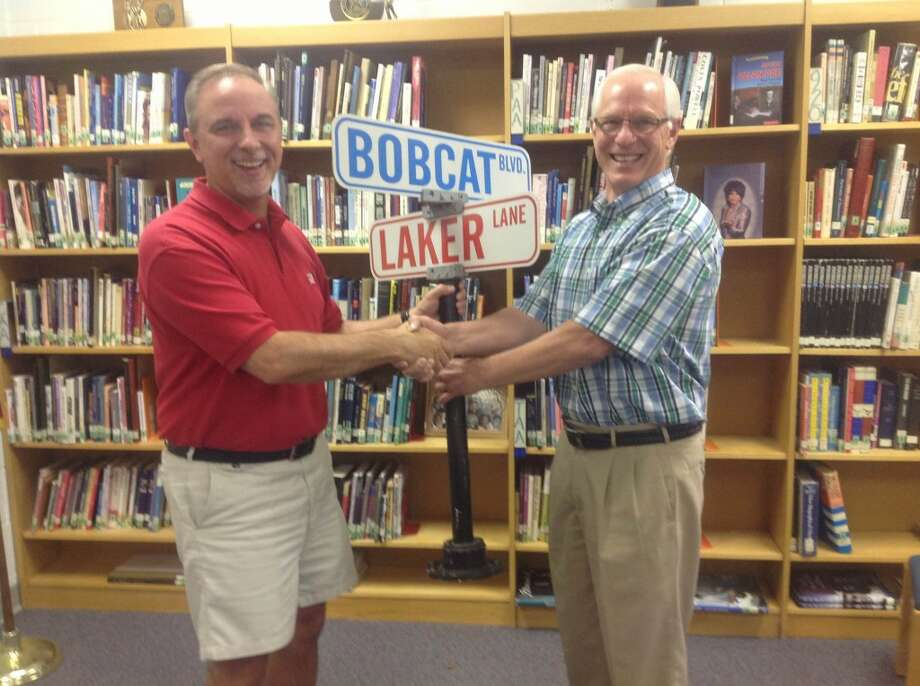 Kaleva Norman Dickson/Bear Lake schools dual superintendent Mike Matesich (right) is shown presenting new superintendent Marlen Cordes (left) with a street sign that says Bear Lake Lane and Brethren Boulevard. Greg Webster who was the first dual superintendent of the two school districts gave the sign to Matesich five years ago when he retired. Matesich continued the tradition as he now passed it on to Cordes at his last board meeting.(Courtesy photo)