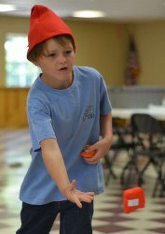 Tyler Fraley, 8, of Wellston, tosses a bean bag Tuesday at the Wellston Library's Gnome Day.