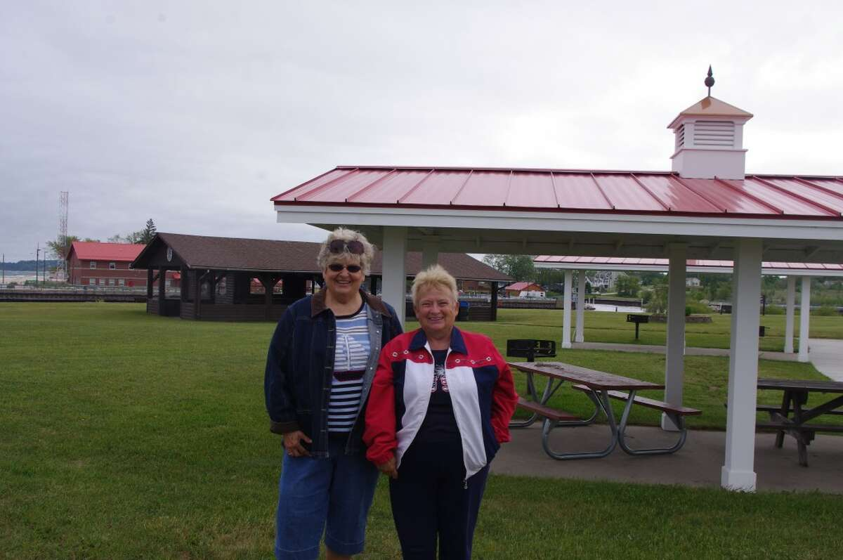 Martha Alberts (left) and Rose Sweigart, members of the Manistee Lions Club, stand next to one of the refurbished picnic shelters. The Lions Club is raising money to refurbish the large picnic pavilion in the background so it will be of similar design. (Dave Yarnell/News Advocate)
