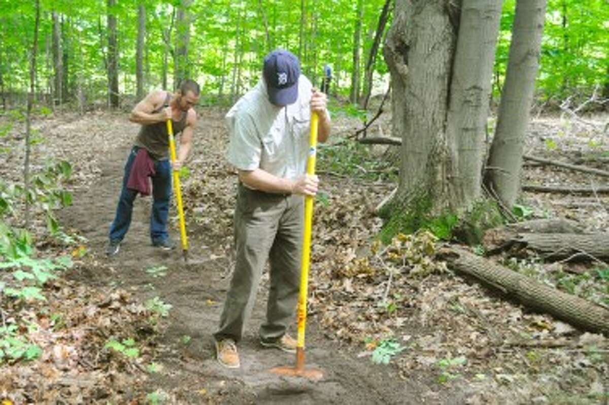Mark Macoun, of Chicago (left), and Mark Deode, of Detroit, used McLeods to pack down dirt at the Arcadia Dunes C.S. Mott NaturePreserve.