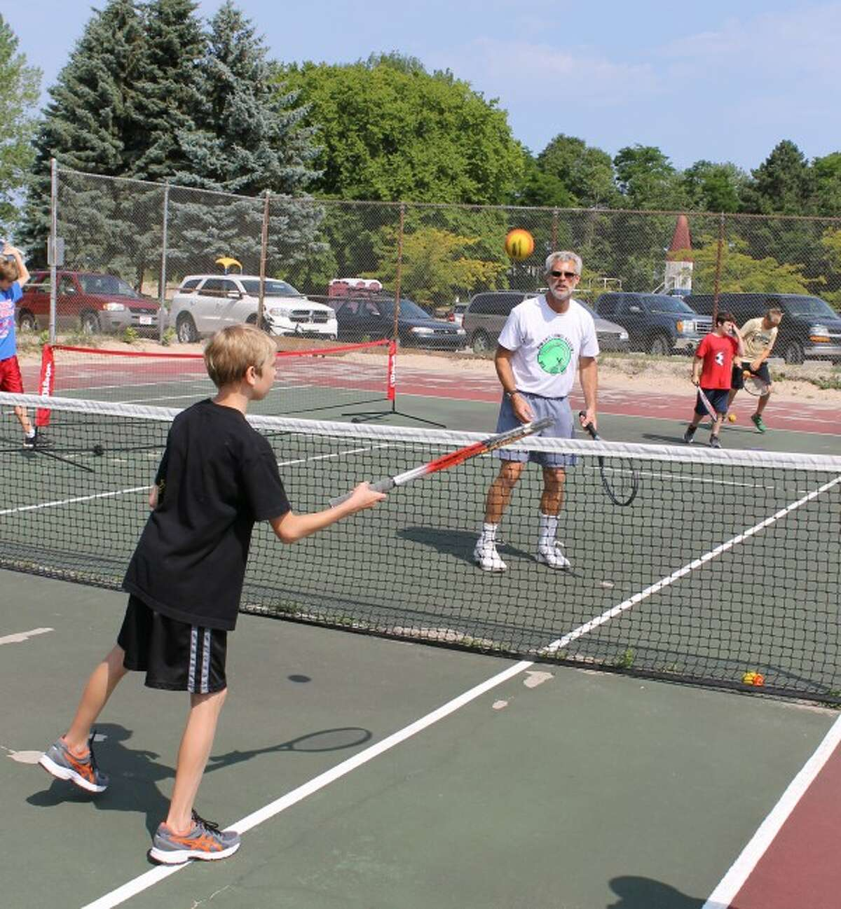 Instructor Greg Sheffield and Ian Kamaloski practice volleying and making shots at the net.