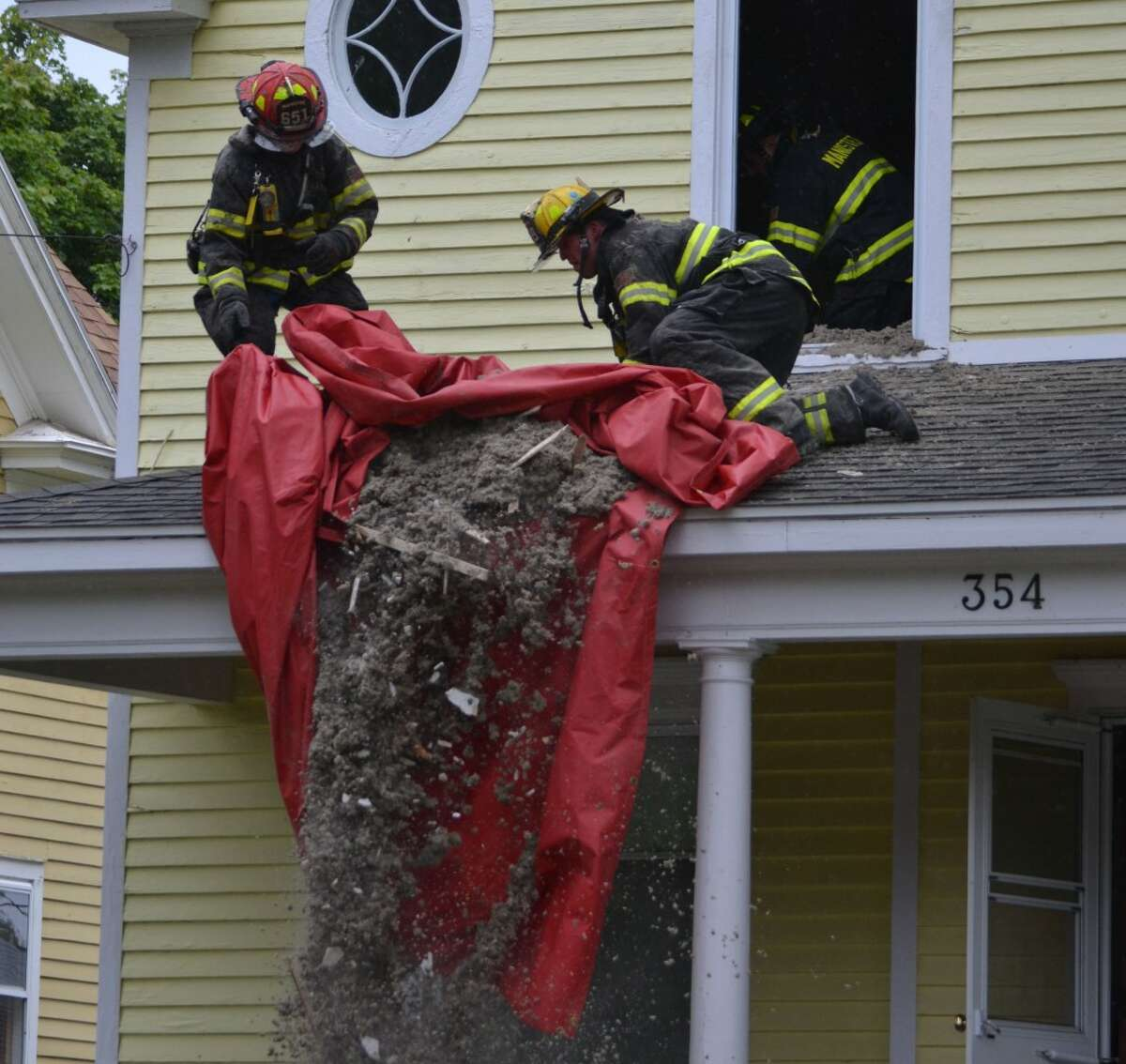 Firefighters dump debris from the second floor of a house on 5th St. in Manistee. They were removing insulation to contain an electrical fire, which broke out in the attic on Sunday afternoon. (Meg LeDuc/News Advocate)