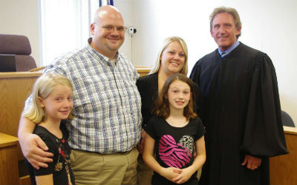 The Duby family is all smiles shortly after Brianna (center) became a part of the family by adoption. From left to right are Morgan Duby, Paul Duby, Brianna, and Probate Judge Thomas N. Brunner. (Dave Yarnell/News Advocate)
