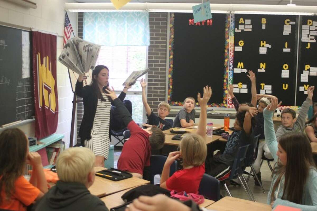 Kennedy Elementary School fifth grade teacher Jaclyn Trahan passes out copies of the News Advocate for her students to take part in the Newspapers in Education program.