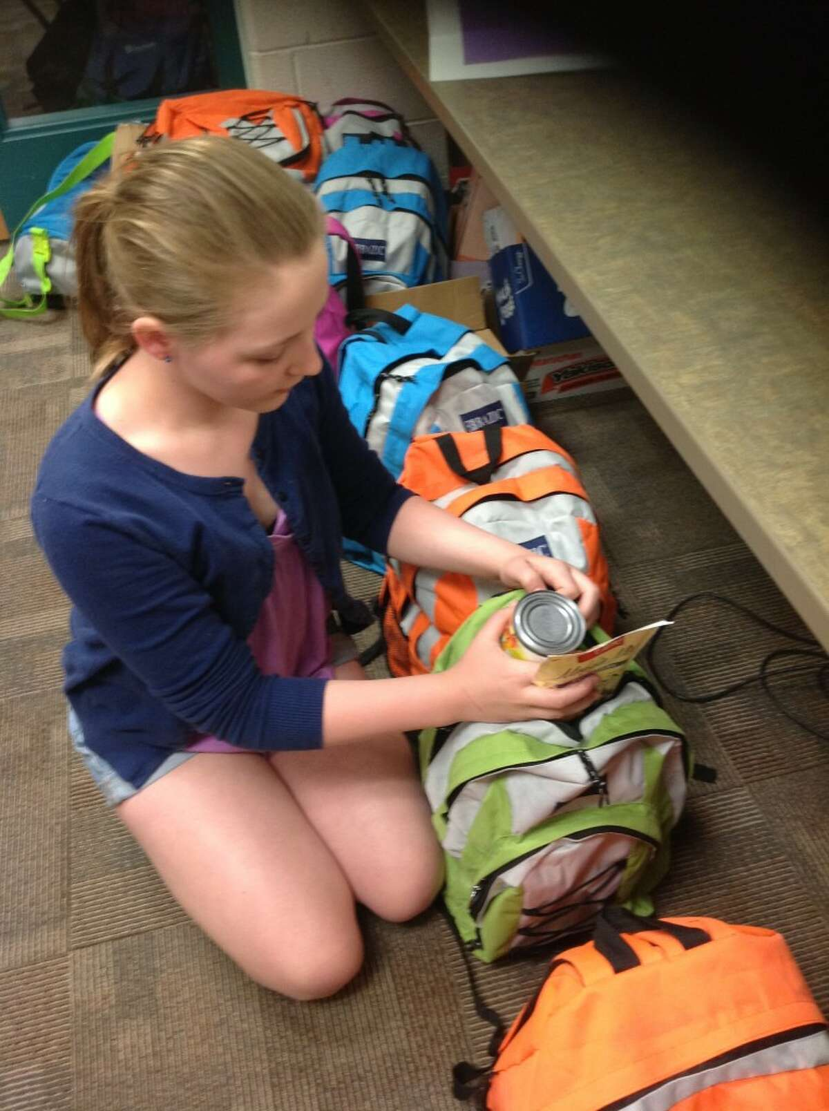 Katy Beeman concentrates on filling up another Portager Pride Pack and placing it next to the ones that have already been filled. Student council members have been doing the fundraiser as a way to help students in need.