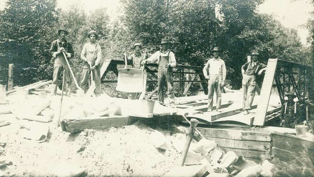 This early 1900 group of bridge builders work hard on fixing a bridge on one of Manistee's county roads.