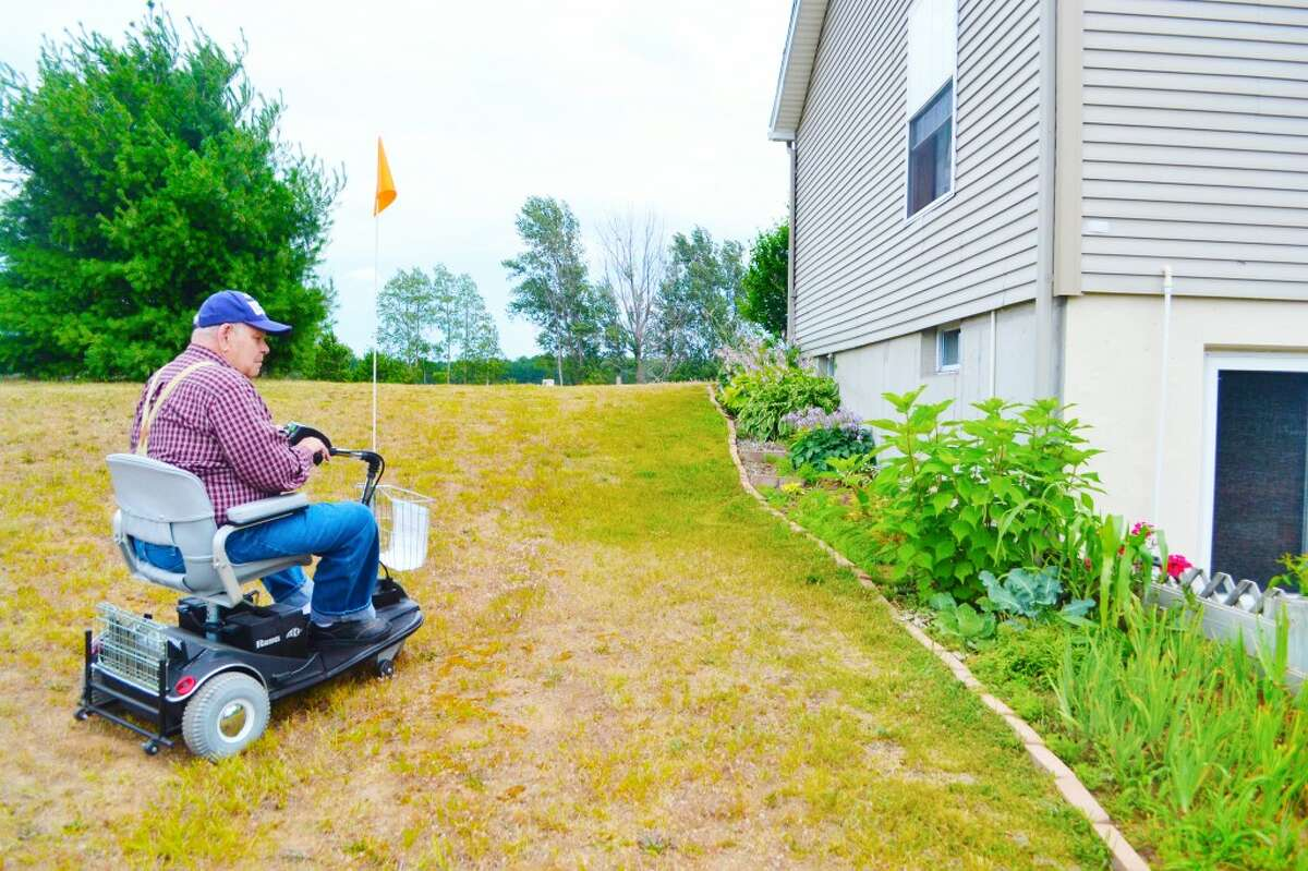 FLOWERS: The scooter that the American Legion donated to John Harwell allows the veteran to access his basement and his wife's flower garden, where he likes to spend time. (News Advocate photos/Meg LeDuc)