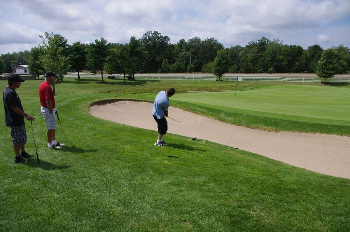 Ben Radlinski attempts a chip shot over the sand trap onto the green during the FiveCAP Golf for Warmth event held Friday at Manistee National Golf & Resort. Looking on are Aaron Haywood (left) and Bob Haywood. (Dave Yarnell/Staff Writer)