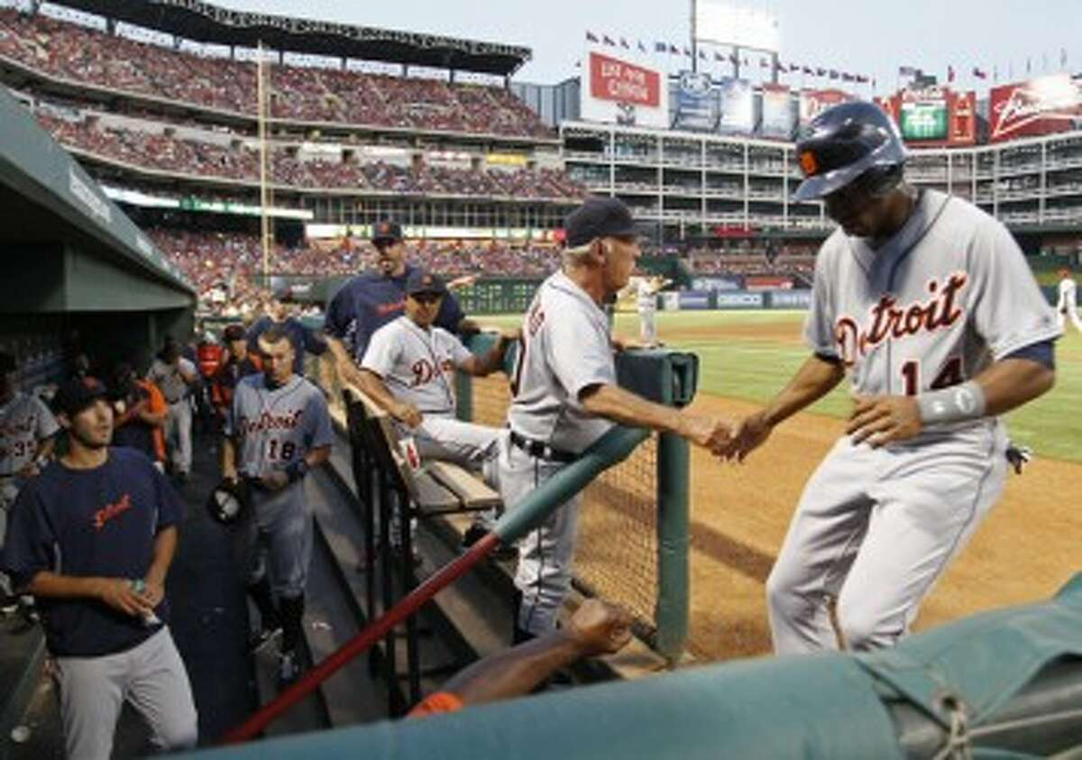 Tigers center fielder Austin Jackson (14) scores on a Miguel Cabrera hit in the the fourth inning drawing a greeting from Detroit manager Jim Leyland in the dugout at Rangers Ballpark in Arlington on Friday. (Paul Moseley/Fort Worth Star-Telegram/MCT)