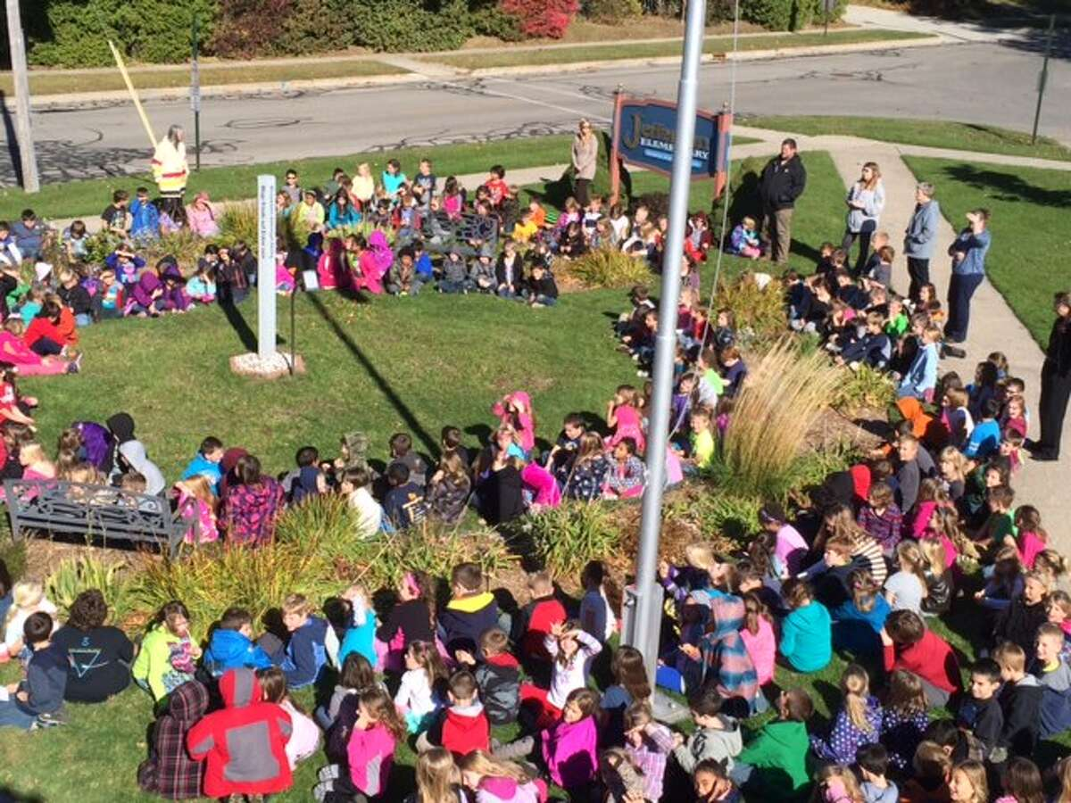 Students at Jefferson Elementary School gather around the school's Peace Pole for an annual ceremony to remember the importance of peace.
