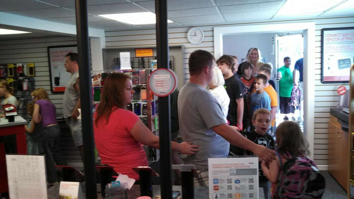 People stretch out of Holmes Verizon LLC on Saturday to receive a free backpack filled with school supplies. The store gave away 150 backpacks in less than an hour.