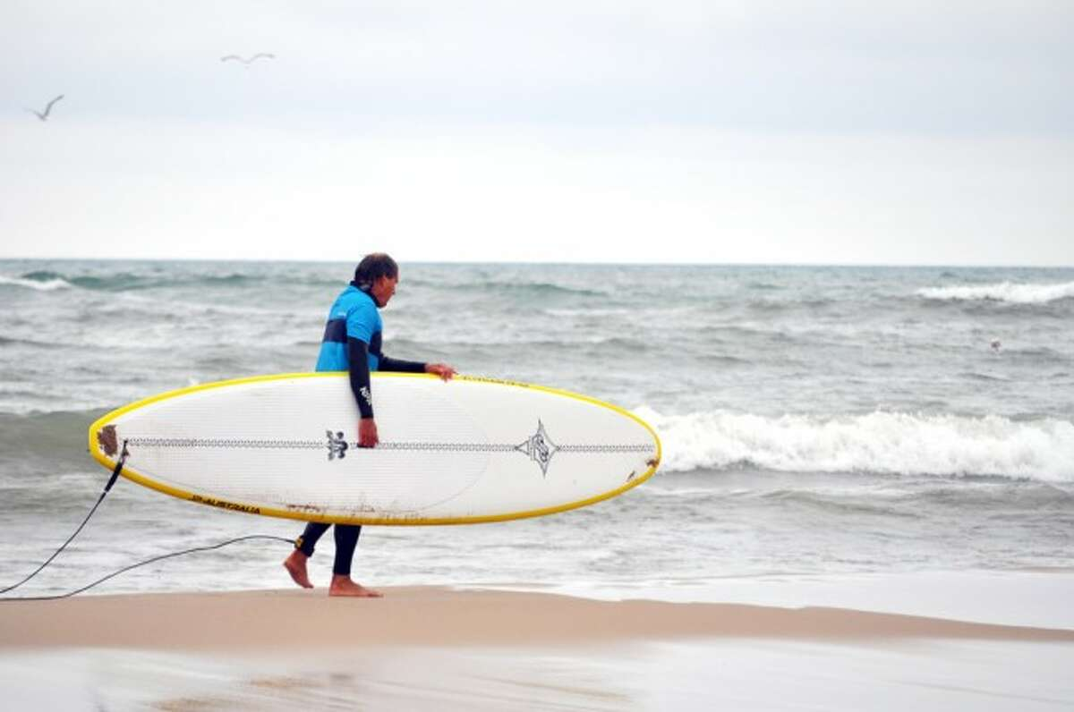 Several surfers took advantage of chest-high waves on Tuesday at Manistee's First Street Beach despite cool temperatures.