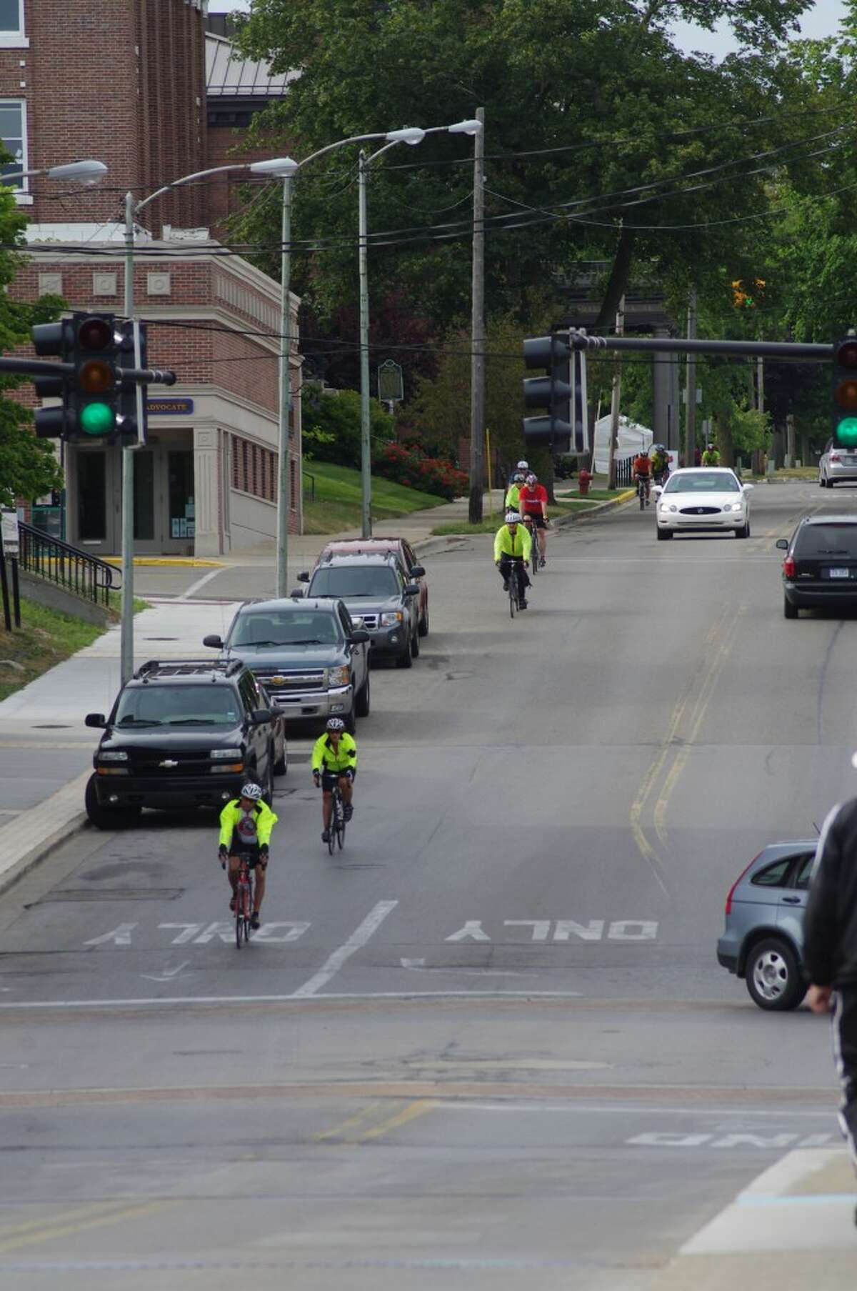 A steady stream of bicyclists traveled through Manistee on Monday as part of the League of Michigan Bicyclists 27th Annual Shoreline West Bicycle Tour. They enjoyed rolling down the hill on Maple Street toward River Street. (Dave Yarnell/News Advocate)
