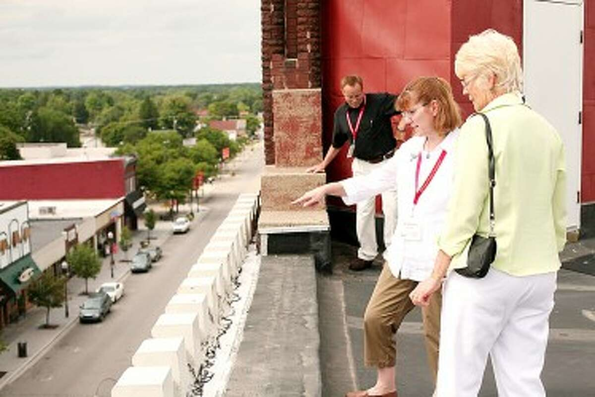 Manistee Mayor Colleen Kenny (center) and Big Rapids Clerk Roberta Cline look over the edge of the top of the Nisbett Building. A tour of the Nisbett and Fairman buildings was the final stop on a day-long tour of Big Rapids as part of a mayor exchange program between the two cities. (Pioneer News Group File Photo)