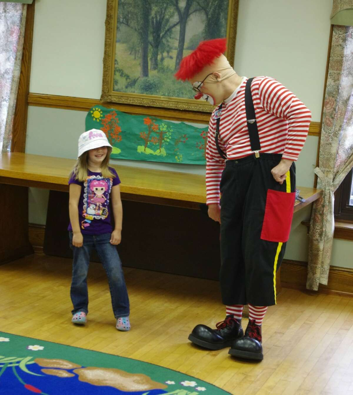 Ava Heuer came to the front to assist clown J.P. Ballyhoo at the Manistee Library on Tuesday. Ballyhoo was in town to promote the Kelly Miller Circus, which will be in Manistee at the industrial park on Washington Avenue for two performances on Aug. 21. (Dave Yarnell/Staff Writer)