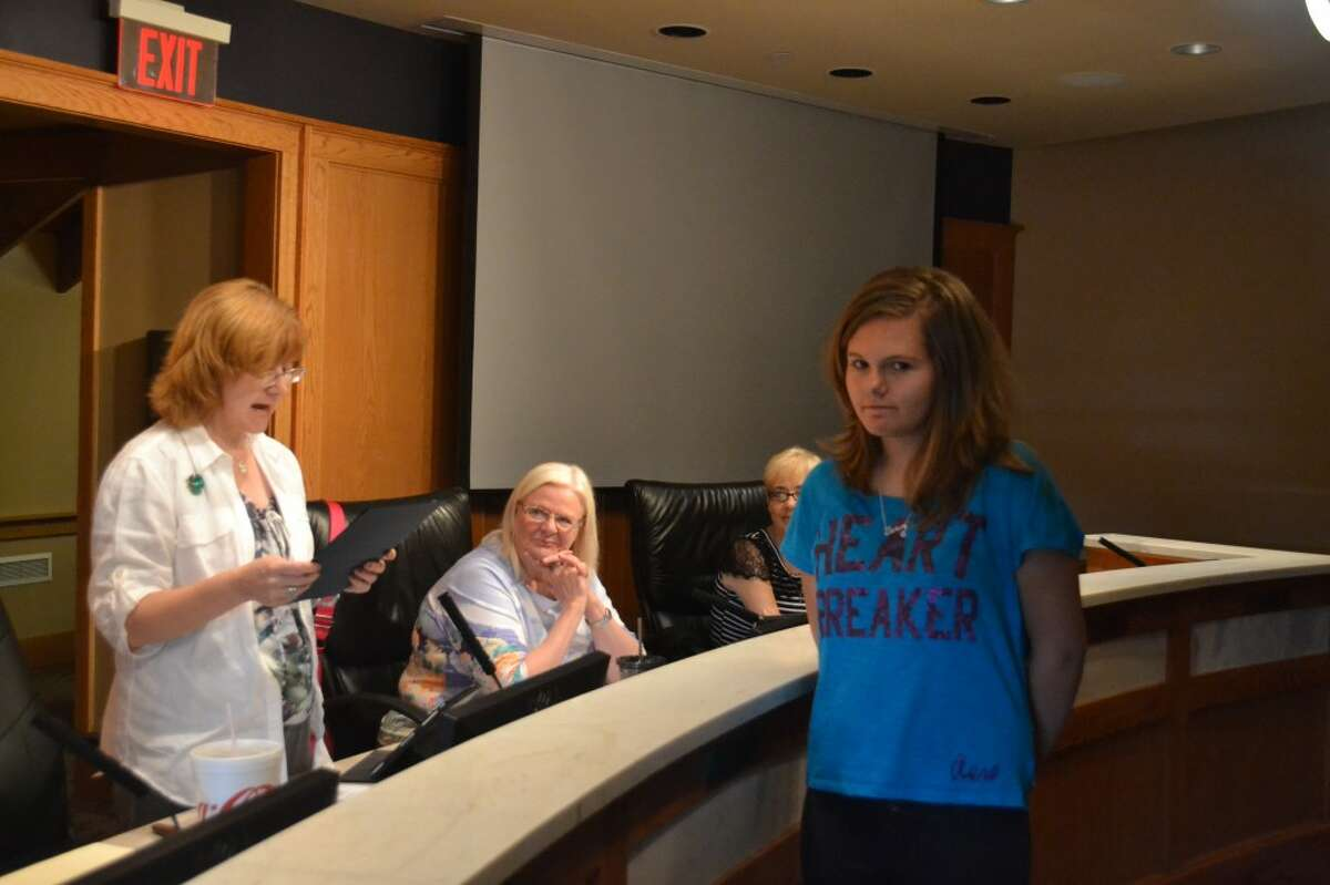 At Tuesday's Manistee City Council meeting, (LEFT TO RIGHT) Mayor Colleen Kenny and council members Catherine Zaring and Beth Adams present a resolution of appreciation to 14-year-old Morgan Haywood, who evacuated three children she was babysitting from a burning 5th Street house in July. (Meg LeDuc/News Advocate)