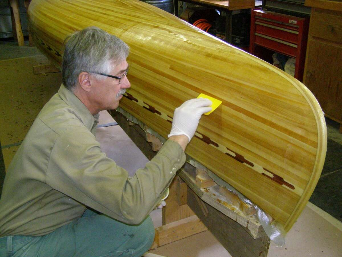 Tim Sapak works on the finish of a wooden canoe he and his wife, Jan, donated to the Manistee Catholic Central Harvest fundraiser.