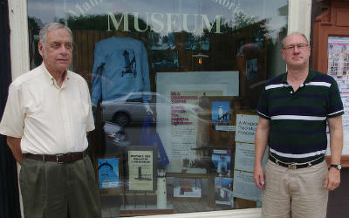 Steve Harold (left) and Thomas G. Stege, both of the Manistee County Historical Museum, pose by the museum's front window display for the upcoming