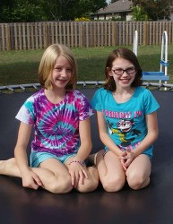 Morgan (left) and Brianna Duby enjoy playing in their back yard, especially on their trampoline.